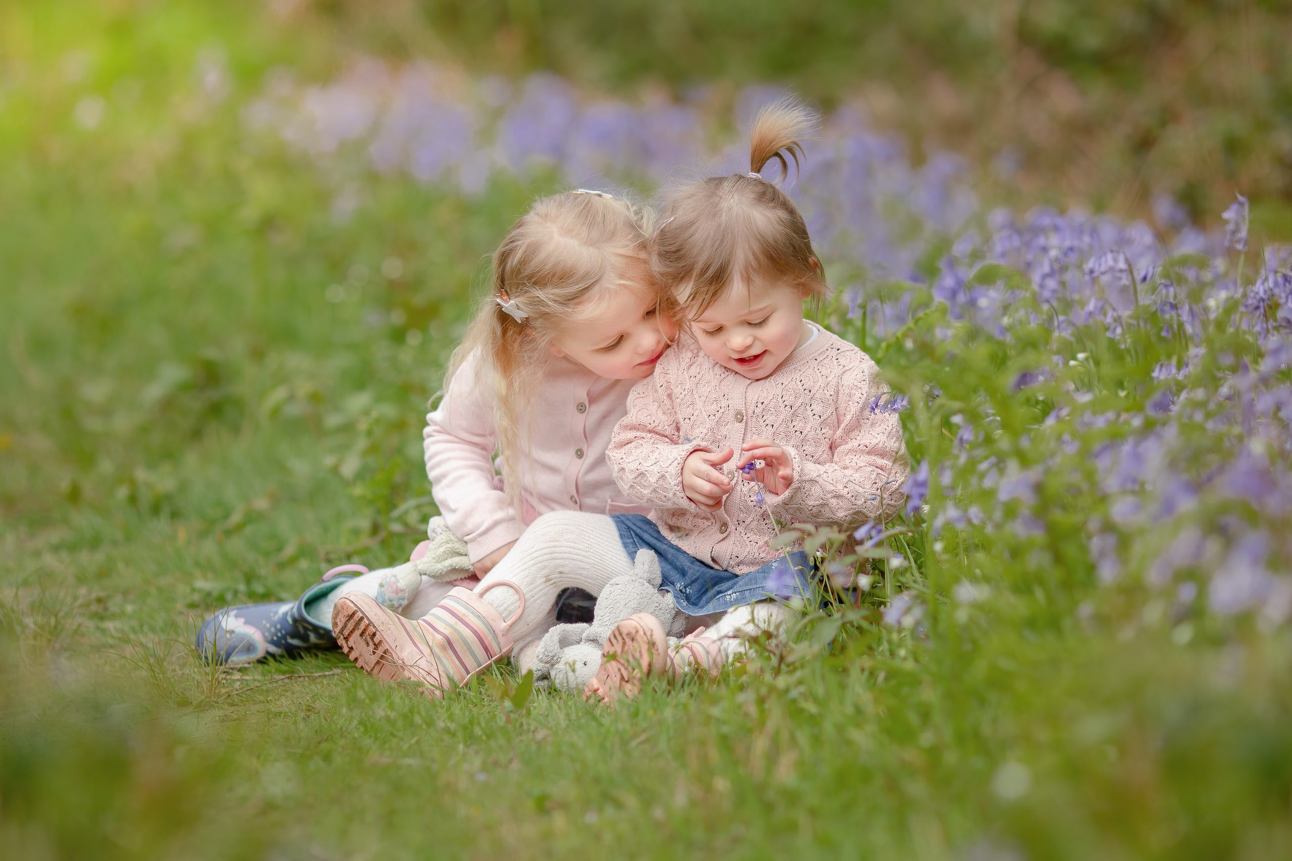 Young sisters sitting together on a bluebell mini photo shoot