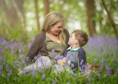 a mother and young son pose amongst a bluebell wood - tunbridge wells photographer