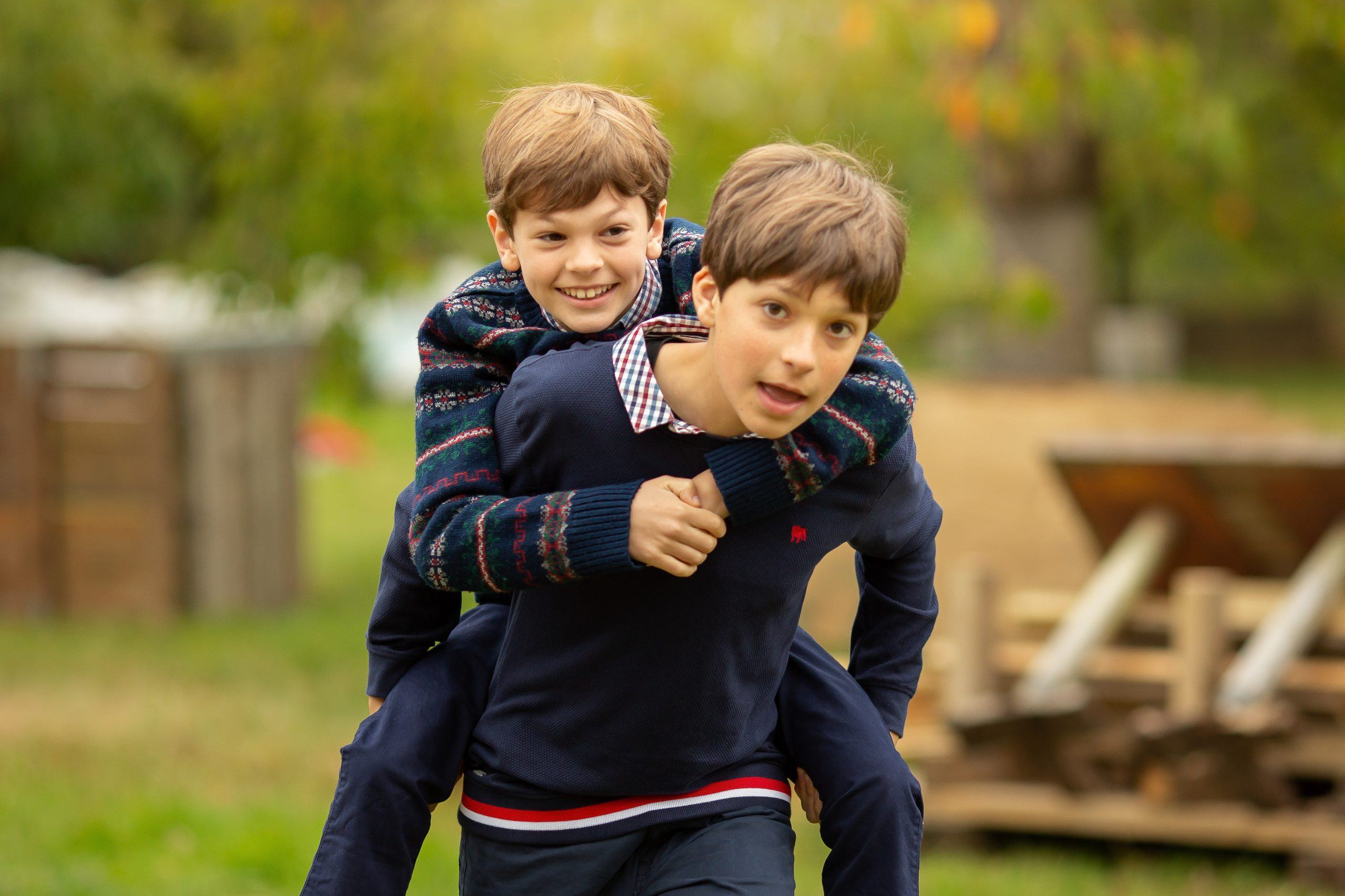 brothers piggy backing on a family photo shoot