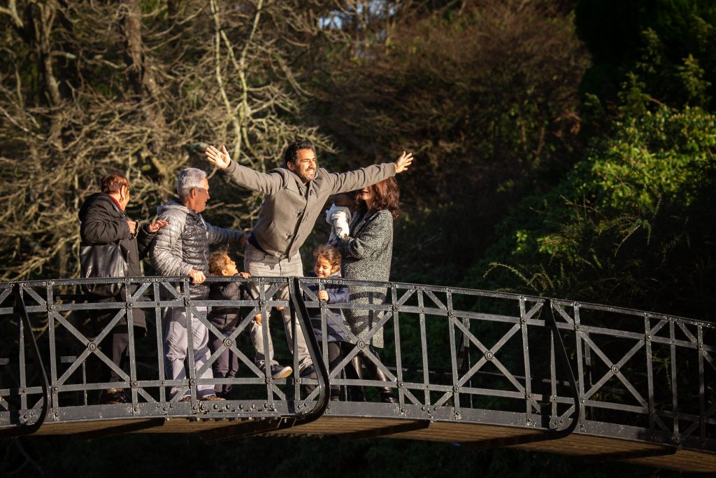 on a family photo shoot, Dad poses on a bridge and does an impression of Leonardo Di Caprio at the front of the ship in Titanic - family photographer tunbridge Wells
