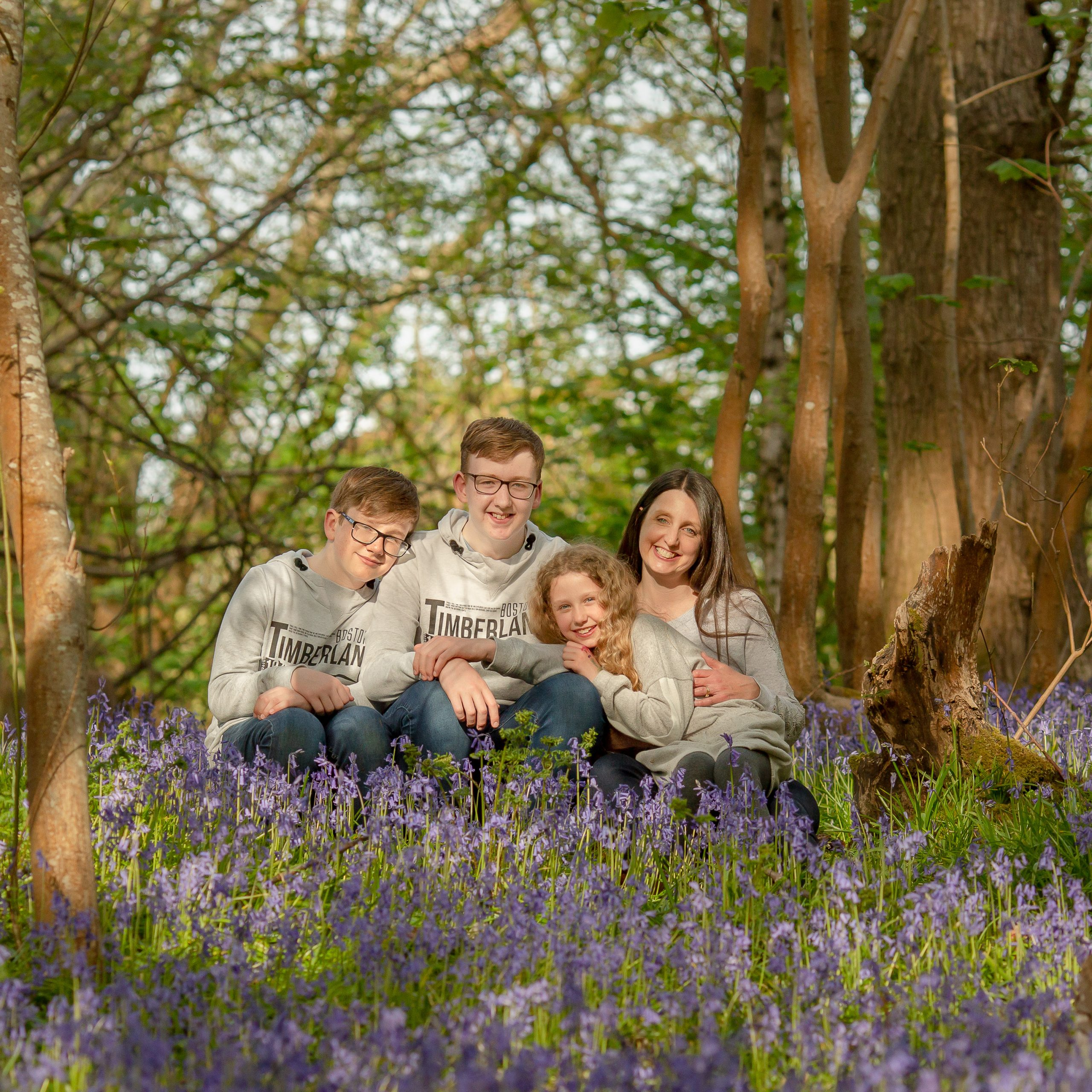 A family sits amongst the bluebells